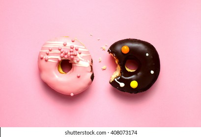 Donuts with icing on pink background. Sweet donuts. Donuts background . Eaten donut.