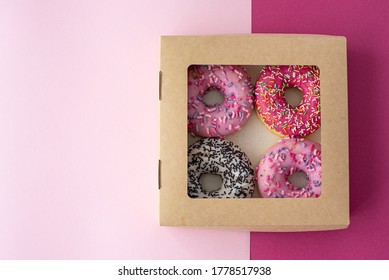 donuts with multicolored glaze in a cardboard box on pink background