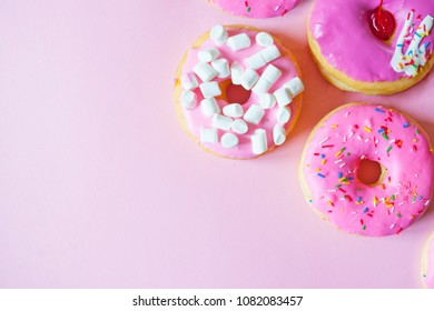 Donuts on link background. Donuts with icing on pastel pink background. Sweet donuts.
