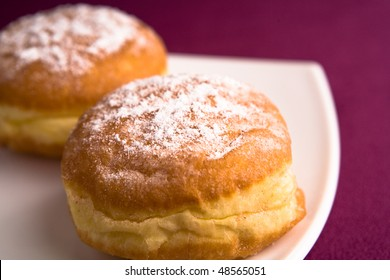 donuts on a white plate on the purple cloth