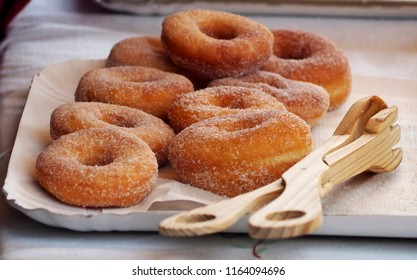 Donuts with sugar on a tray in a bar., On the right a rustic wooden cake tongs to serve them.