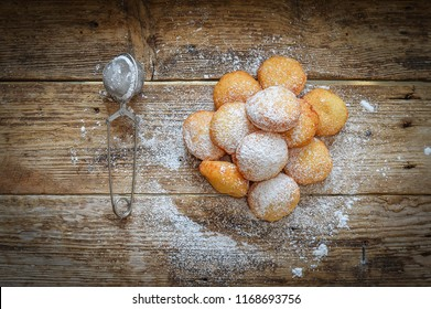Donuts with sugar powder on a wooden background