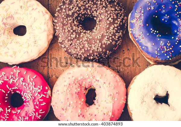 ドーナツ。甘い砂糖料理。デザートのカラフルなおやつ。ガラスのスプリンクル。美味しい料理を食べてごちそう。ベーカリーケーキ。フロスティング付きドーナツ。焼いた不健康な丸。