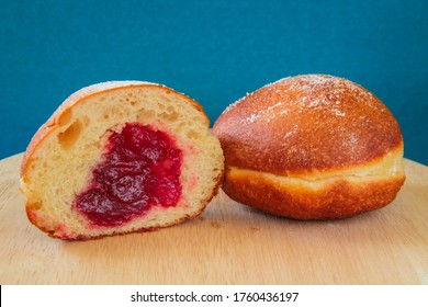 Donuts, two a classic European donuts, one cut with cherry Jam, and one whole with jam filling and icing sugar German donuts, Polish donuts. On a wooden board with a blue background.