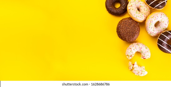 Donuts with various toppings on yellow background. Fat Thursday. Doughnuts