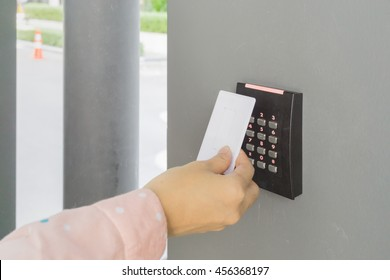 Door access control with a hand inserting key card to lock and unlock door. Security system concept.
