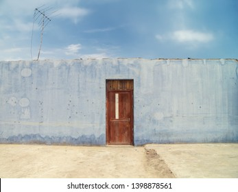 Door in a blue wall and blue sky