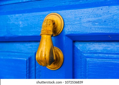 Door with brass knocker in the shape of a hand,  beautiful entrance to the house, vintage decoration