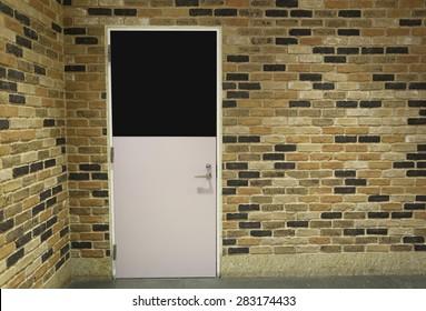 Door and brick wall in home interiors.