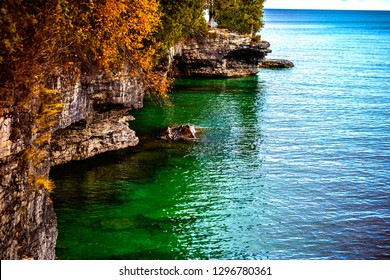 Door County, Wisconsin coastline of cliffs, caves and coves, covered in fall colored trees and pines atop a rocky landscape next to Lake Michigan.