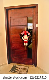 Door decorated with a Santa Claus garland and a rug written Merry Christmas