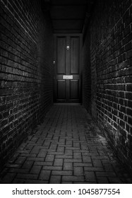Door at the end of a dark alleyway at night