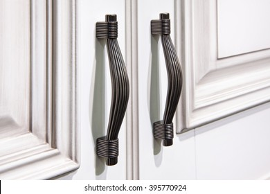 Door furniture handles and white door.