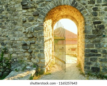 The door, the gate in the wall, open to the rays of the sun, Stari Bar, Montenegro