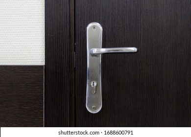 Door handle close-up elements. Closed wooden door in a modern style in the interior. Door handle, accessories for interior design. Home interior of an apartment or office.