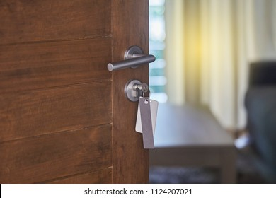 Door handle with key tag.Hotel or apartment door half open while lighting glowing in blur living room background, selective focus