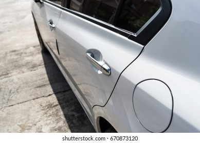 door handle on left side of white car parking on the street