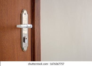 Door handle of a simple wooden door on the entrance of an apartment