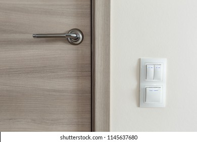 Door handle and white lighting switches on wall at modern apartment
