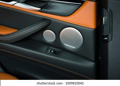 Door handle with windows control buttons of a luxury passenger car. Red and black leather interior of the luxury modern car. Speaker and door panel