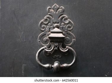 Door handle in the wooden door - forged, openwork in medieval style. (Lyon, France).