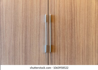 Door handles made of shiny metal, straight lines. The cabinet wall is beautiful.