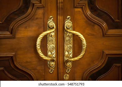 Door handles with an old double door. Golden Handle Door Entrance. Luxury gold handle. classical style golden door handle on brown wood. switches on the wall. Close up of double antique gold plated