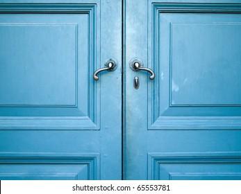 Door handles with an old double wood door painted with blue