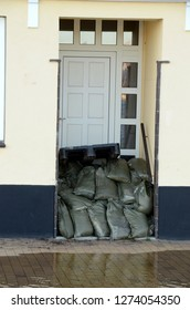 A door has been blocked with sandbags due to an approaching storm surge, the water already stands close to the door.