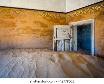 Door held open by encroaching sand dunes inside an abandoned building in an old mining town in Namibia.