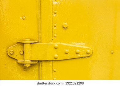 door hinge closeup view on yellow painted abstract grunge background