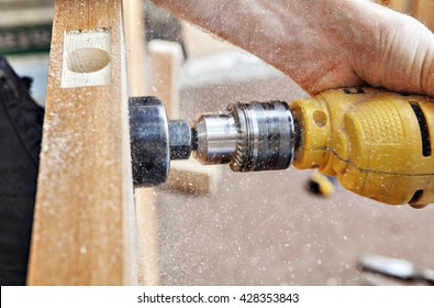 Door installation, drilling a big hole through the door using yellow electric drill with hole saw drill bits for lock doorknob, close-up.