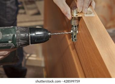 Door installation, installing deadbolt lock using power drill, close-up.