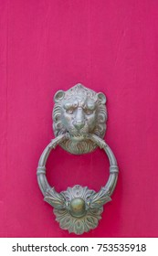 Door knob in the form of a detailed lion's head on a bright pink background - traditional on Malta