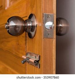 door knob and keyhole on wooden door, close up image