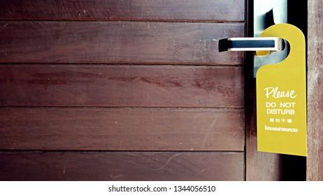 Door knob with label on a door handle. Leaflet design on entrance doorknob. Don't disturb sign and make up room.