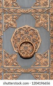 Door knocker on ancient wooden door in Kiev, Ukraine, close up