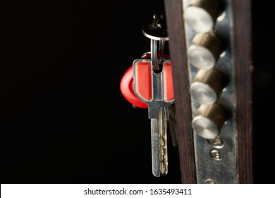 the door lock with the handle and a key. Focus on keys. - Shutterstock ID 1635493411