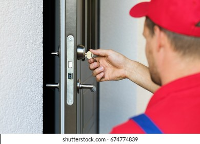 door lock service - locksmith working in red uniform
