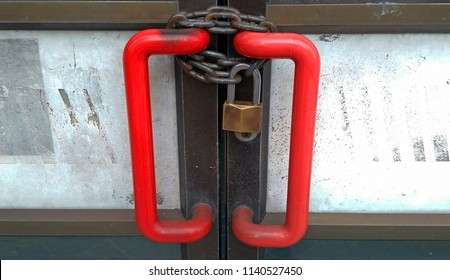 A door with a locked chain. Business closed.