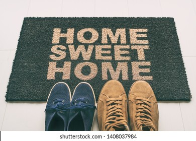 Door mat Shoes at front entrance of condo apartment. Written welcome sign Home Sweet Home welcoming homeowners at new house moving in couple's pairs of sneakers lying on the floor.