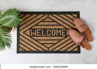 Door mat with word WELCOME and shoes on floor, top view