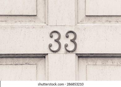 Door number 33 thirty three conceptual image closeup