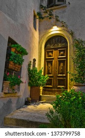 Door in an old house decorated with flower pots and flowers at night