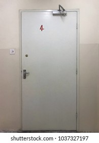 A door on a wall, number four on it and an electric switch on the left of the door
