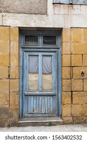 Door with peeling paint and an old iron ring embedded in the wall for tethering horses on a street in the bastide town of Castillones, Southwest France.