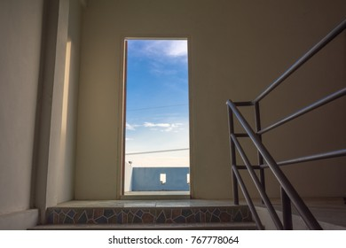 The door to the rooftop and the bright sky.