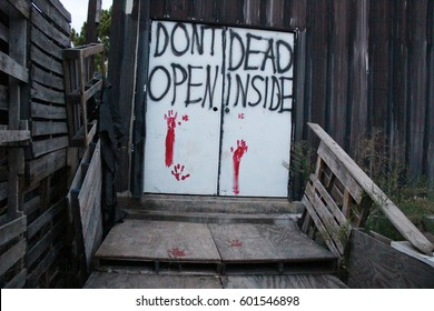 """Door with a sign """"don't open, dead inside"""" and bloody handprints visible. The building is a part of zombie hunt decoration for Halloween."""