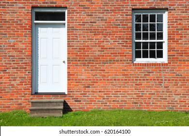 Door and single window on brick wall