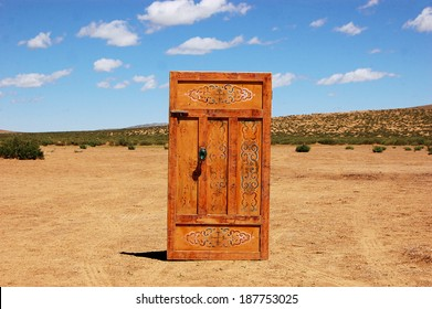 Door standing in the middle of the desert, leading nowhere